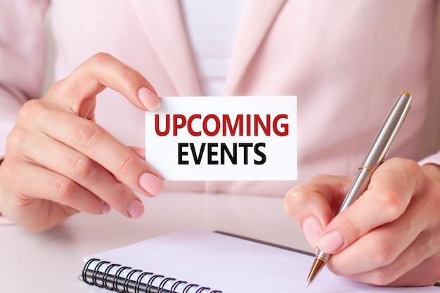Une femme écrit dans un cahier avec un stylo en argent et une carte avec texte: événements à venir. fond rose, vue de face. concept d'entreprise et d'éducation.