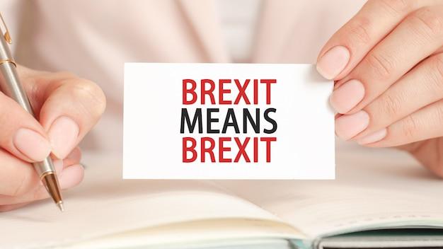 Une femme écrit dans un cahier avec un stylo en argent et une main tenant une carte en papier blanc avec du texte : brexit signifie brexit. fond rose, vue de face. concept commercial et financier.