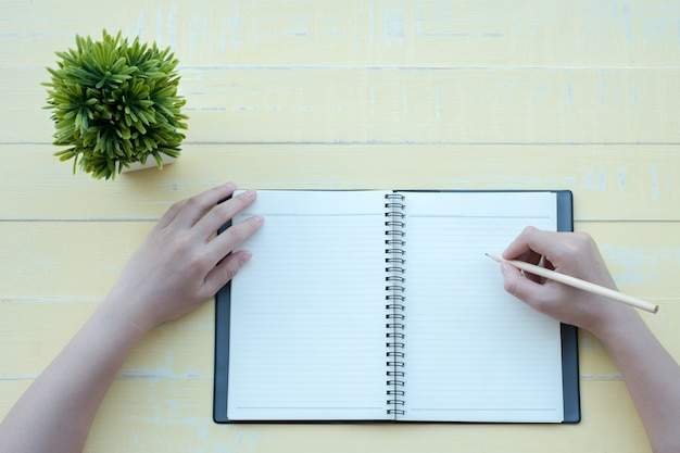 La femme a écrit le livre avec un livre d'argile sur fond jaune. la vue de dessus