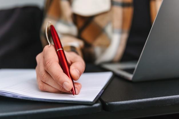 Une femme écrit une note dans un cahier avec un stylo à bille rouge. photo en gros plan