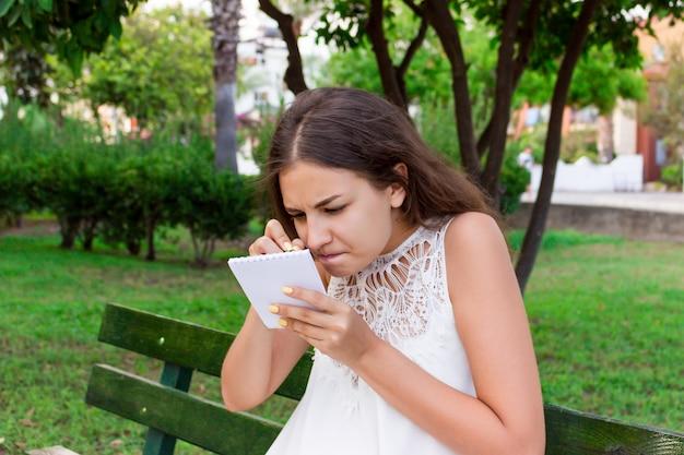 Une femme écrit ses idées excitantes dans son bloc-notes avec une grande concentration