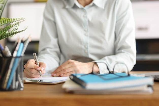 Une femme écrit avec un stylo dans des documents sur le lieu de travail