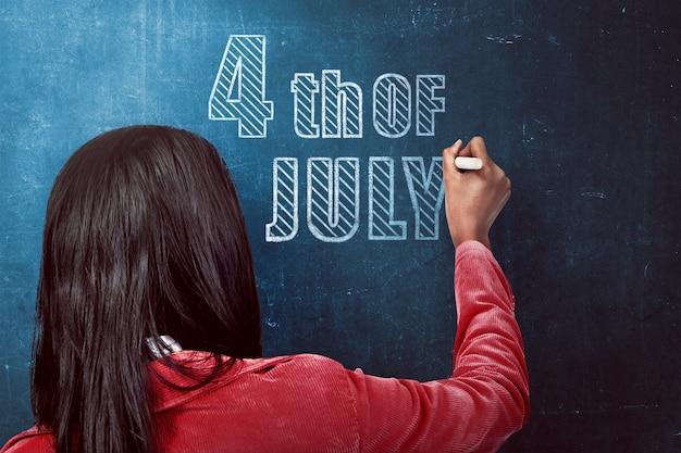 Femme écrivant le 4 juillet au tableau