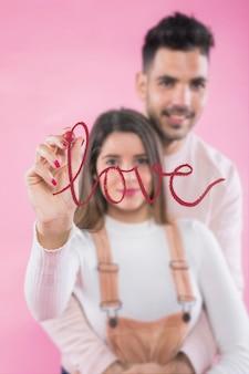 Femme écrivant l'amour sur le verre avec le rouge à lèvres