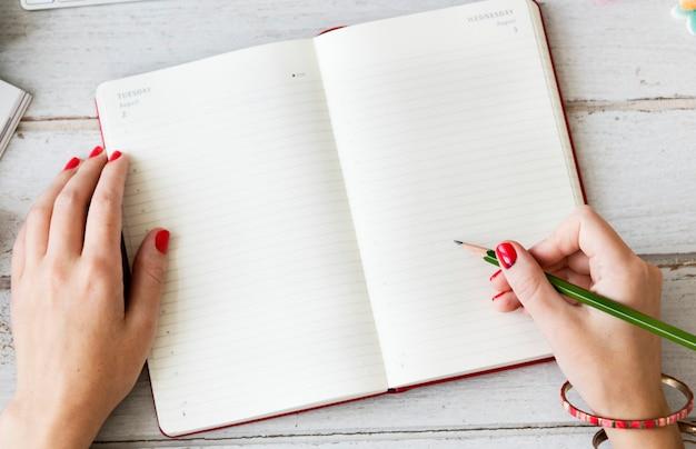 Femme écrivant sur un bloc-notes