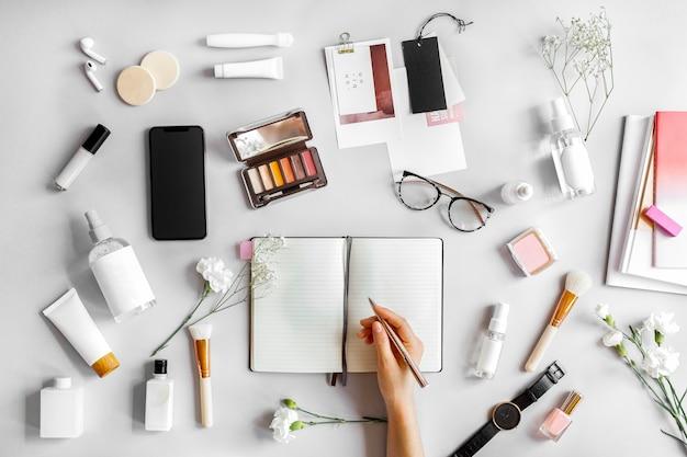 Femme écrivant sur un cahier entouré de produits de beauté