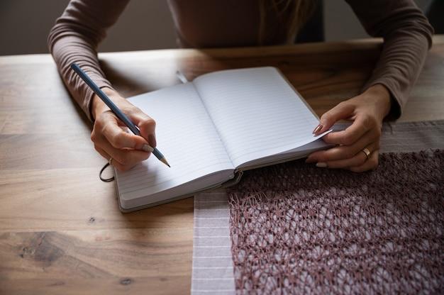 Femme écrivant dans un bloc-notes vierge avec un crayon sur une table à manger en bois. conceptuel de travailler ou d'étudier à domicile.