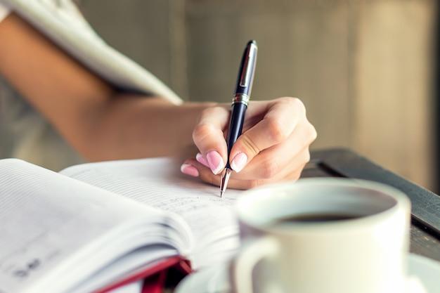 Femme écrivant dans le bloc-notes.