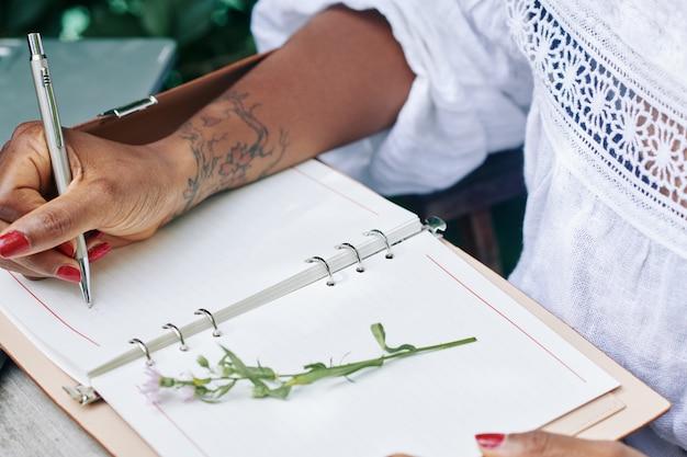 Femme écrivant dans le bloc-notes