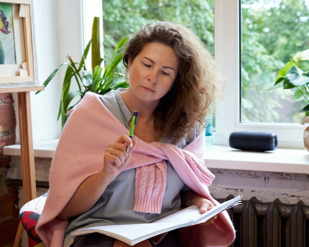 Femme écrivant dans un cahier, journée de planification dans le journal.