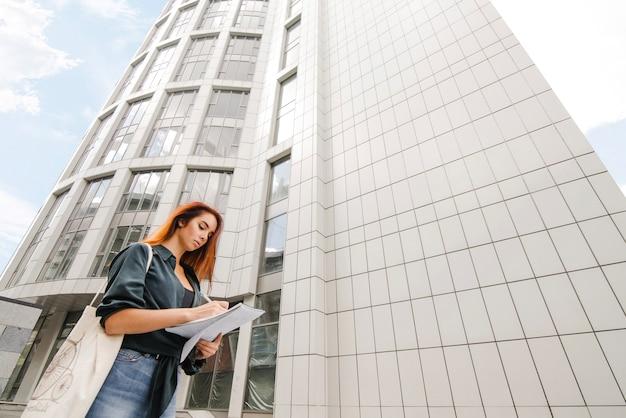 Femme écrivant dans des journaux au bâtiment