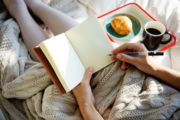 Femme écrivant un journal de cahier au petit déjeuner le matin