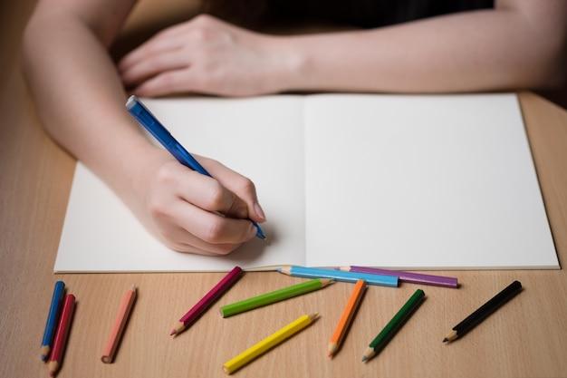 Femme écrivant à la main sur un livre vierge