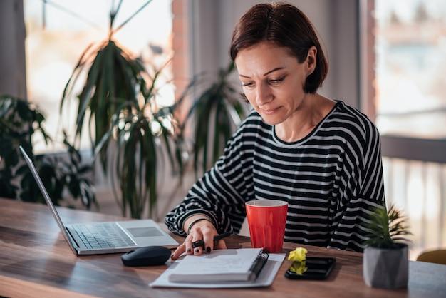Femme écrivant des notes dans un cahier