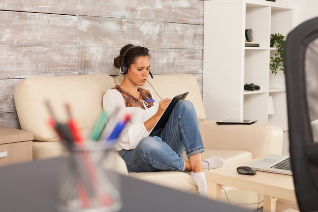 Femme écrivant des notes sur le presse-papiers et portant des écouteurs lors d'un appel vidéo de travail.