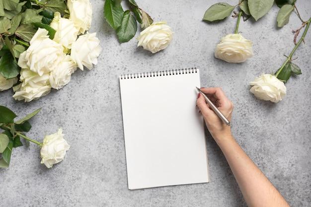 Femme écrivant ou planifiant la liste de contrôle sur blanc de roses blanches sur fond gris. vue de dessus, espace copie.