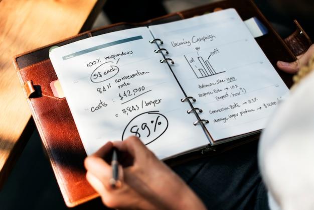 Femme écrivant et planifiant la stratégie commerciale