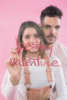 Femme écrivant sois ma saint-valentin sur un verre avec du rouge à lèvres