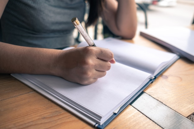 Femme écrivant son idée sur ordinateur portable dans un café
