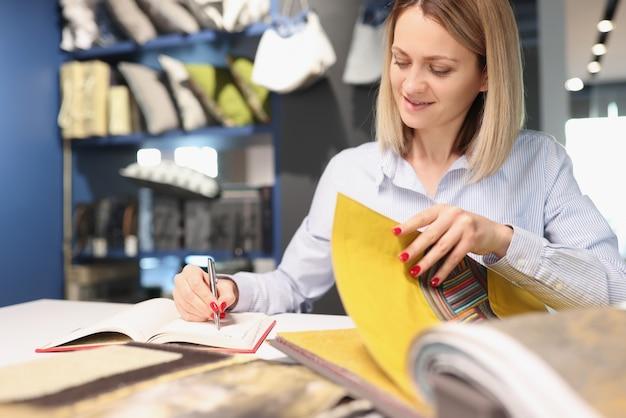 Femme écrivant avec un stylo dans un cahier et feuilletant un catalogue avec des tissus. rideaux à coudre