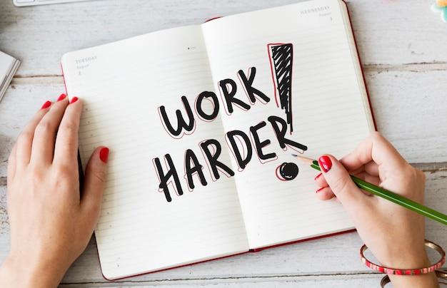 Femme écrivant travailler plus dur sur un cahier