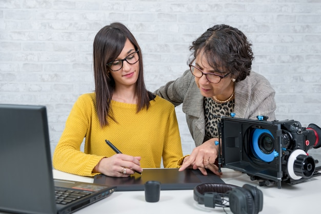 Femme éditeur de vidéo et jeune assistant à l'aide d'une tablette graphique