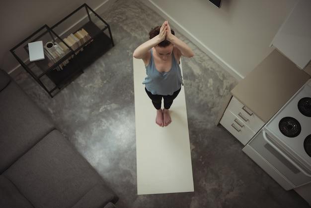 Femme effectuant du yoga à la maison