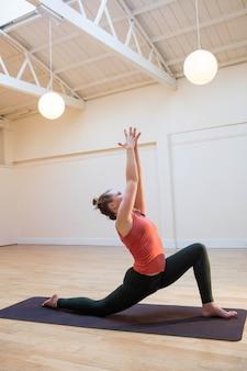 Femme effectuant faible fente pose sur le tapis d'exercice