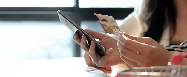 Femme effectuant un paiement en ligne sur son téléphone portable avec carte de crédit pour faire des achats en ligne