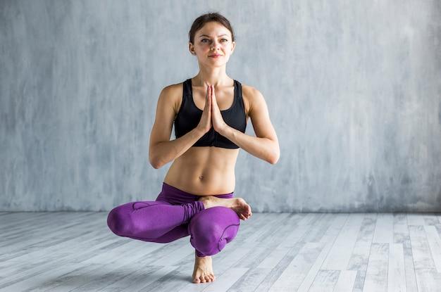 Femme effectuant une posture de lotus debout sur son pied