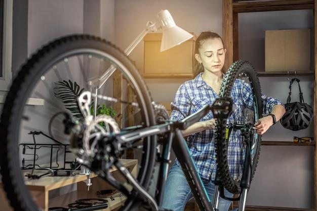 Une femme effectue l'entretien de son vélo de montagne. concept de fixation et de préparation du vélo pour la nouvelle saison