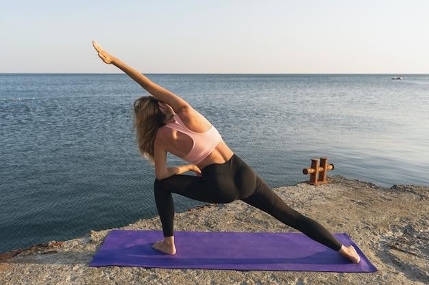 Une femme effectue l'exercice utthita parshvakonasana au bord de la mer debout sur un tapis