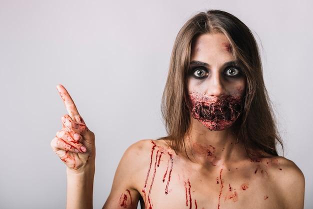 Femme effrayante pointant vers un espace vide