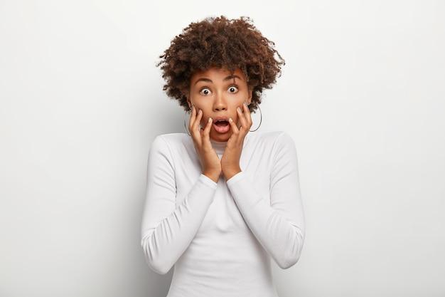 Une femme effrayée aux cheveux bouclés halète de peur, garde les mains sur les joues, ne peut pas croire aux nouvelles choquantes