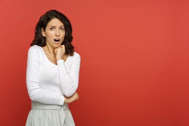 Femme effrayée avec la bouche ouverte de choc ou de dégoût, choquée par les mains jointes sur fond de corail