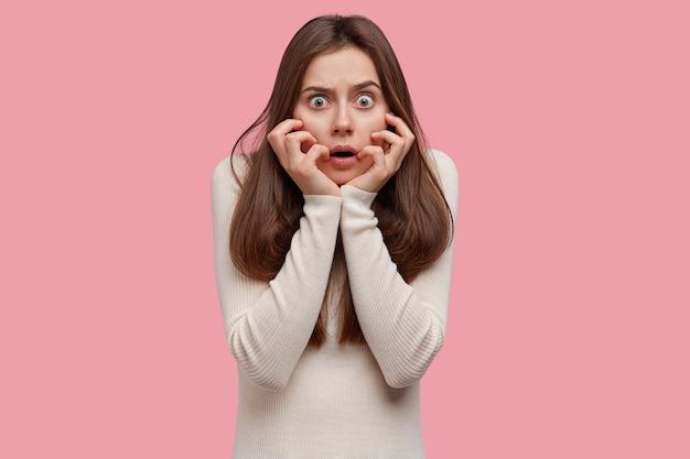 Une femme effrayée et choquée a les yeux largement ouverts, touche les joues, réalise une catastrophe