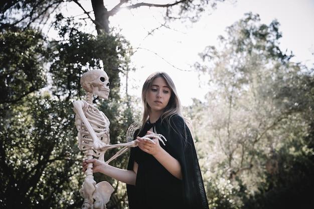 Femme effrayée dans des vêtements de sorcier tenant un squelette
