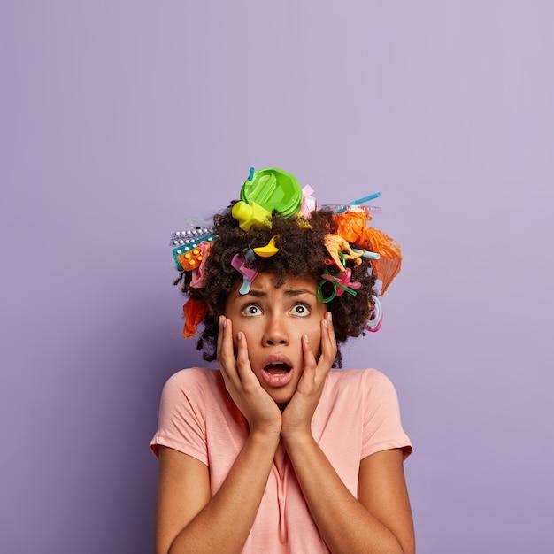 Femme effrayée horrifiée posant avec des ordures dans ses cheveux
