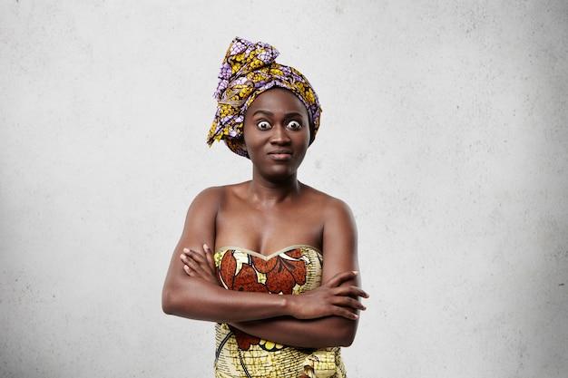Femme effrayée à la peau sombre avec les yeux borgnes et les lèvres charnues debout les mains croisées. femme africaine effrayée