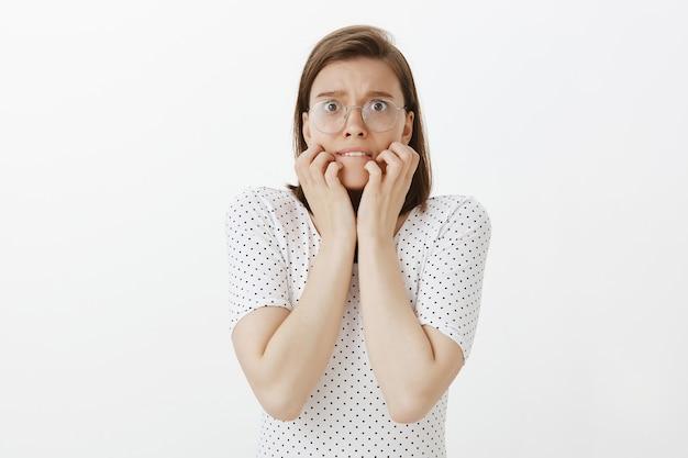 Femme effrayée se mordant les ongles dans la panique, l'air effrayé et frissonnant de peur