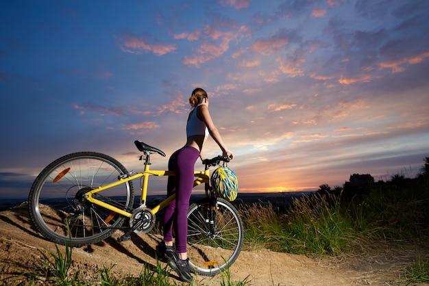 Femme élancée posant avec son dos. cycliste athlétique debout avec vélo jaune, regardant le coucher du soleil et le beau paysage.
