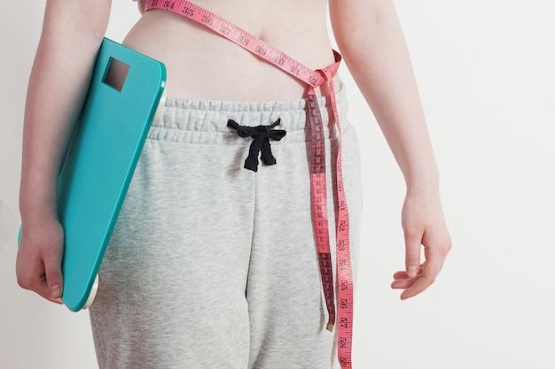 Femme, électronique, balances, bande, taille, contre, mur blanc
