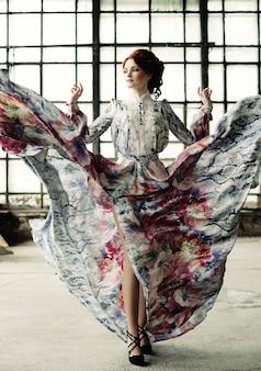 Femme d'élégance avec robe volante dans la salle du palais