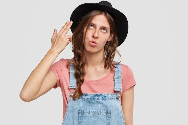 Femme avec élégant chapeau noir et salopette