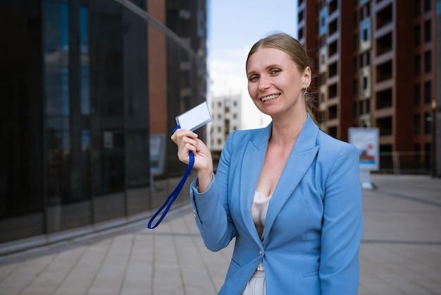 Femme élégante d'affaires dans une veste bleue tient un badge dans sa main contre le mur d'un immeuble de bureaux