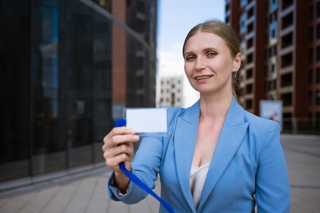 Femme élégante d'affaires dans une veste bleue tient un badge dans sa main d'un immeuble de bureaux