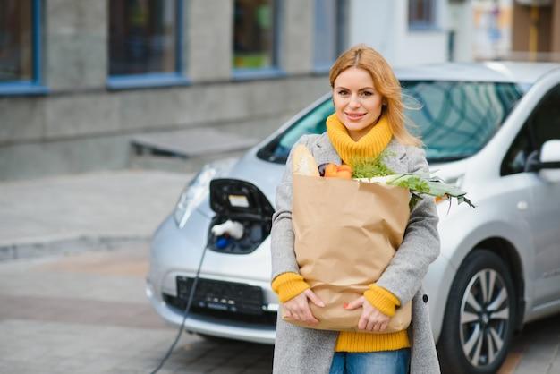 Femme élégante après avoir acheté des produits avec un sac à provisions est debout près de la voiture électrique en charge
