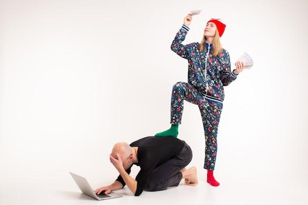 Femme élégante avec de l'argent domine l'homme travaillant à l'ordinateur sur fond blanc