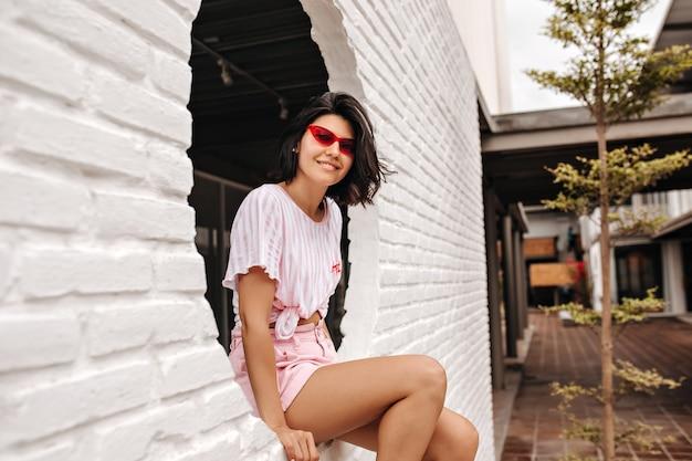 Femme élégante assise sur le mur et regardant la caméra. tir en plein air de la charmante jeune femme posant avec un sourire sincère dans la rue.