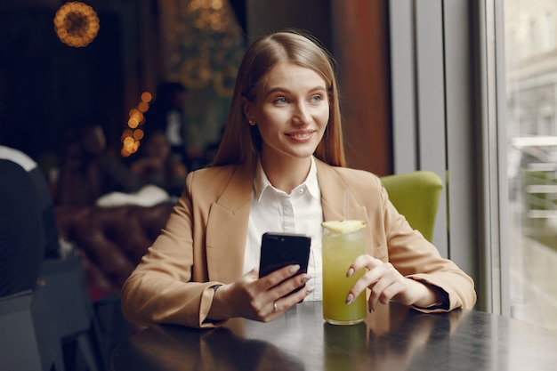 Femme élégante assise à table avec cocktail et téléphone